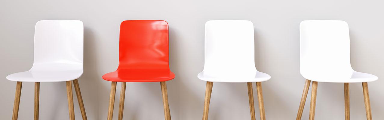 Weiße Stuhlreihe mit einem einzigen roten Stuhl