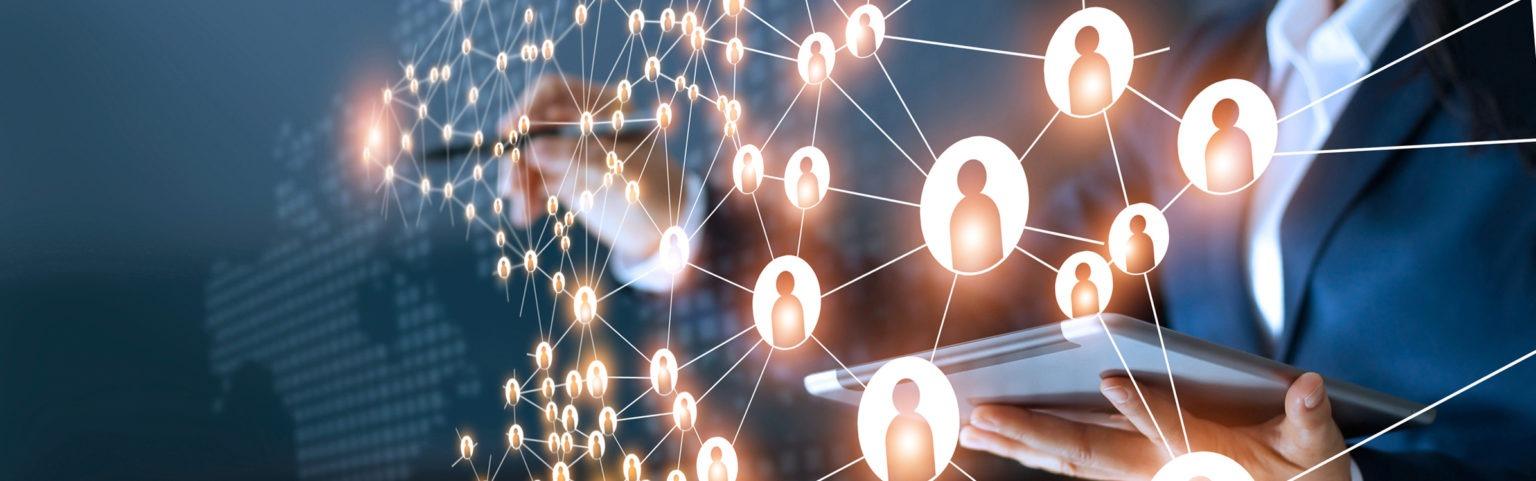Person mit Tablet steht vor Netzwerk aus Personen